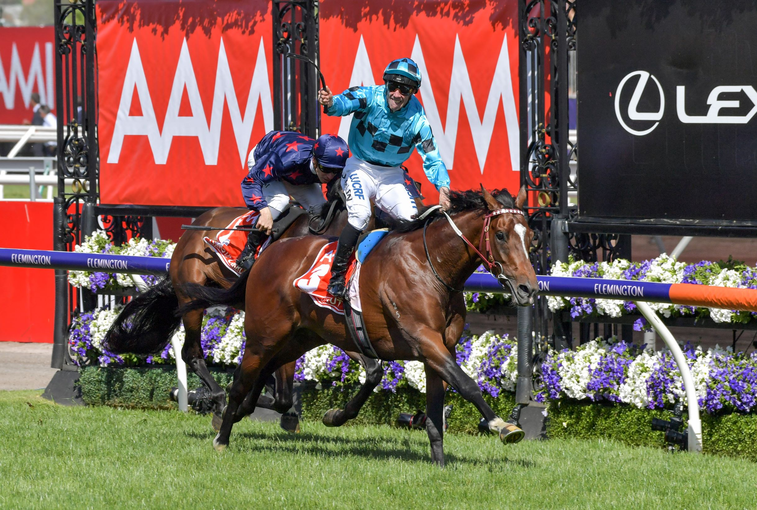 Jockey John Allen celebrates as Extra Brut crosses the line winning the Victoria Derby